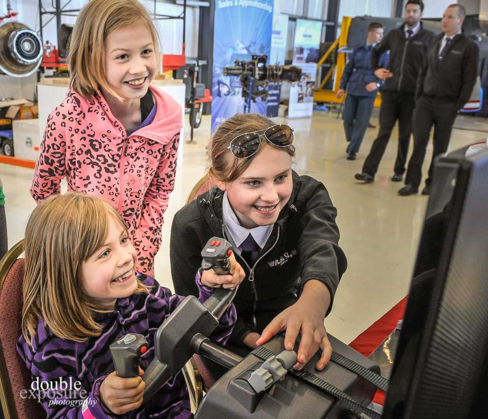A young pilot shows girls how to use a flight simulator.