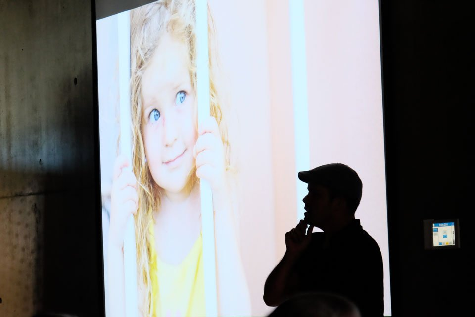 speaker pauses while daughter watches. Event photography.