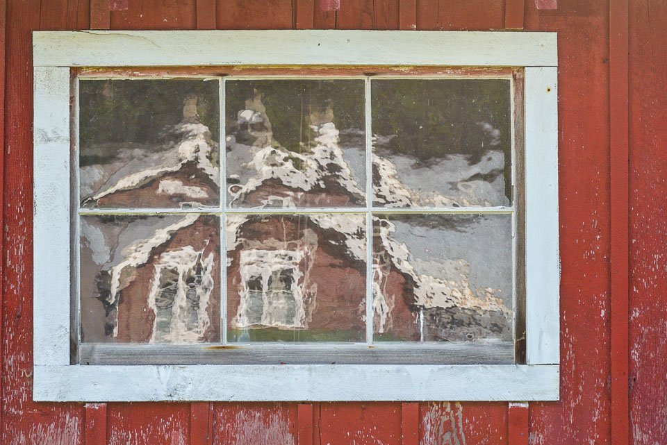 Reflections of the cannery in an old window at Develop Your Creative Vision.