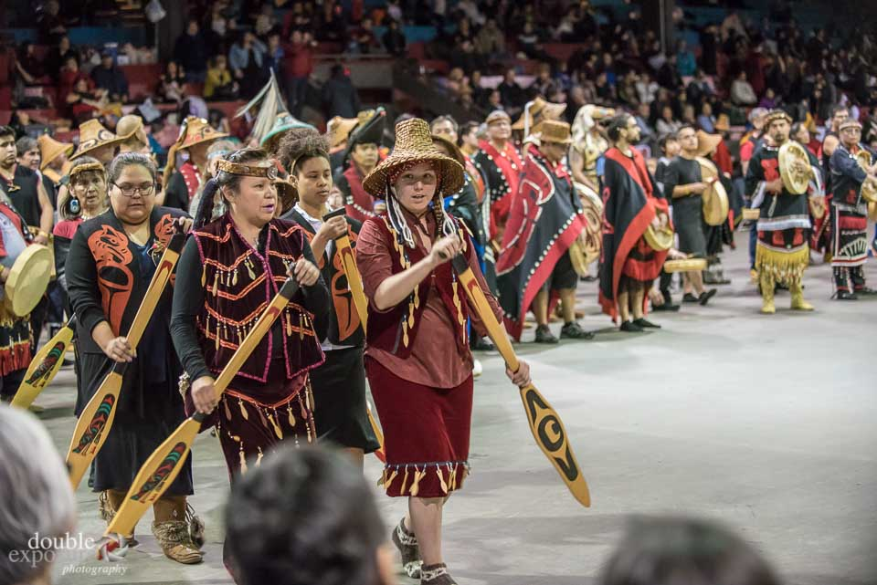 Squamish dancers with paddles enter the dance floor.