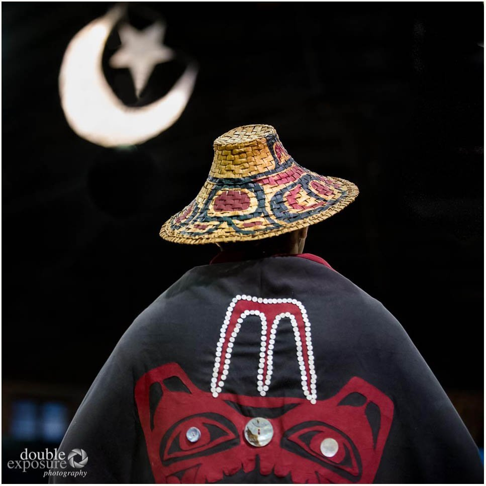 An aboriginal dancer in full regalia under a model of the crescent moon, a sign of good harvests to come