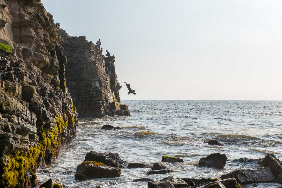 A man dives off a steep cliff into the ocean.