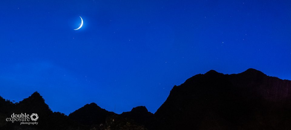 The moon shines on the mountains over Machu Picchu