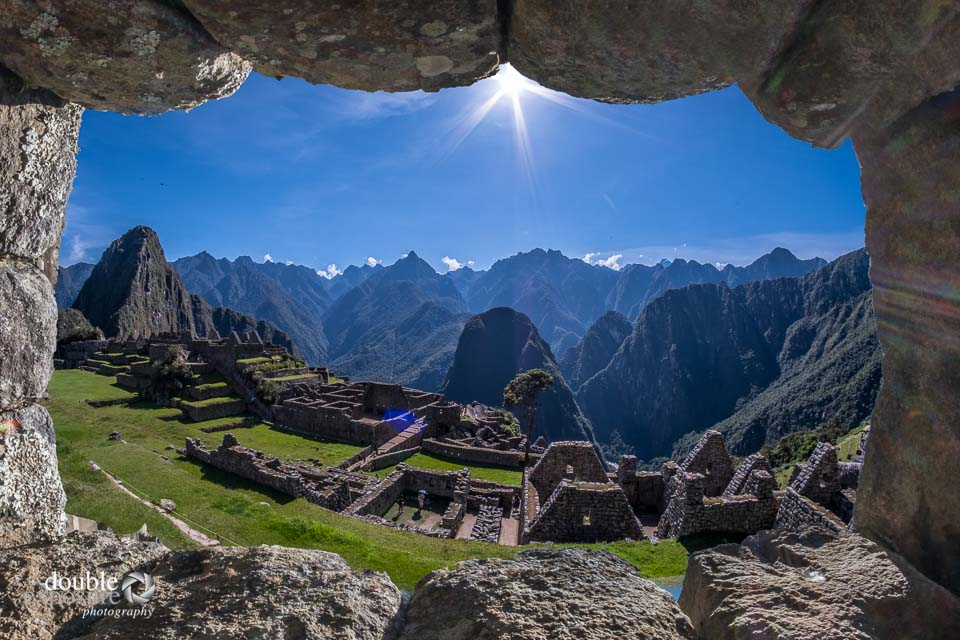 A stone window frames the site of Machu Picchu.