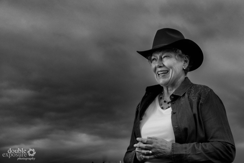 Woman cowgirl against a stormy sky.