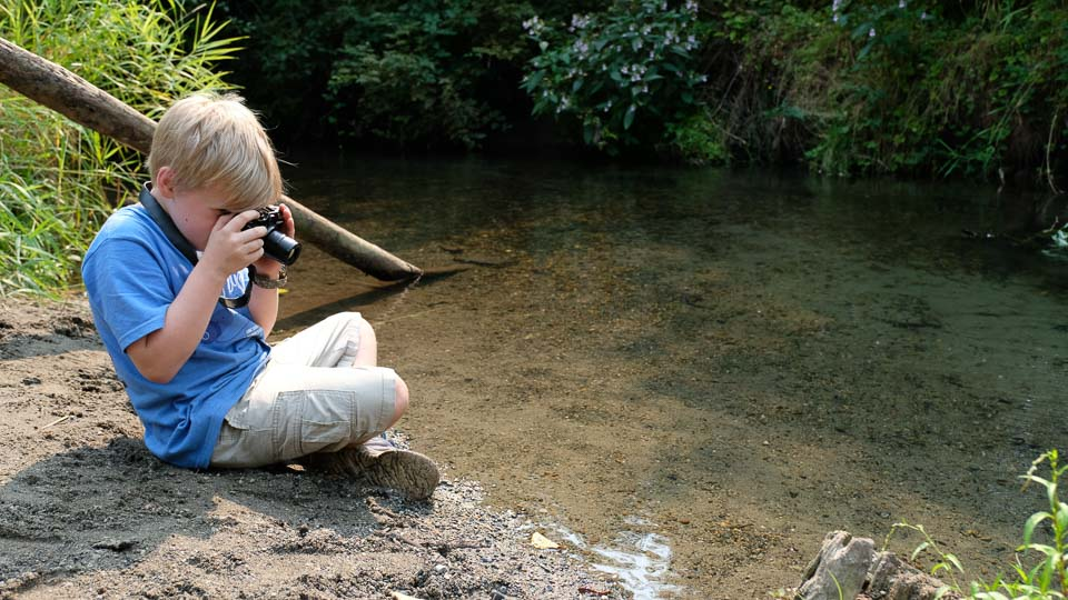 boy with camera on water's edge.