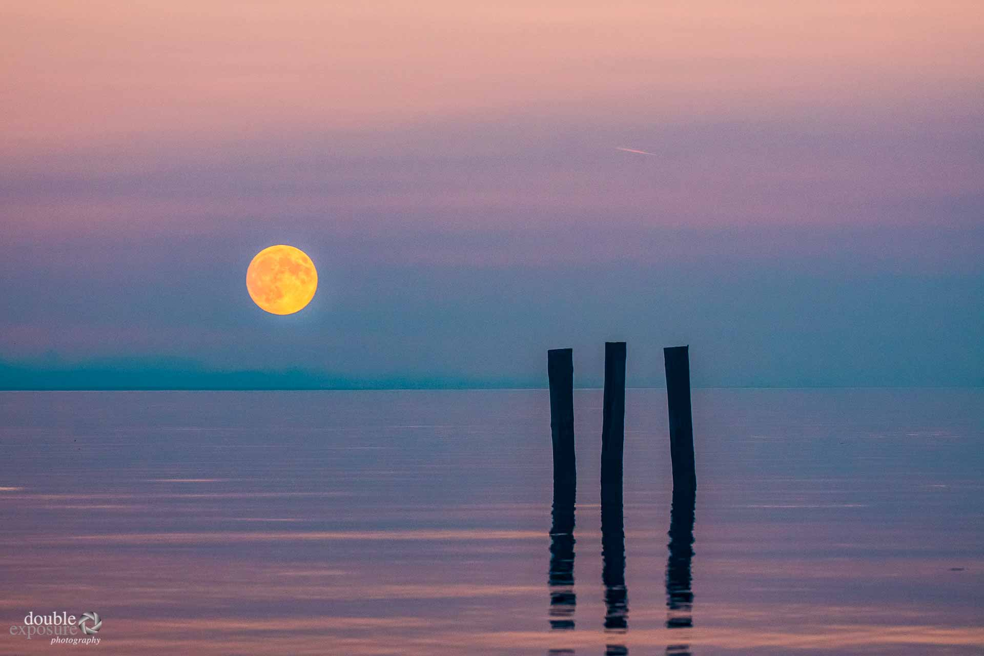 the full moon watches over the evening twilight.