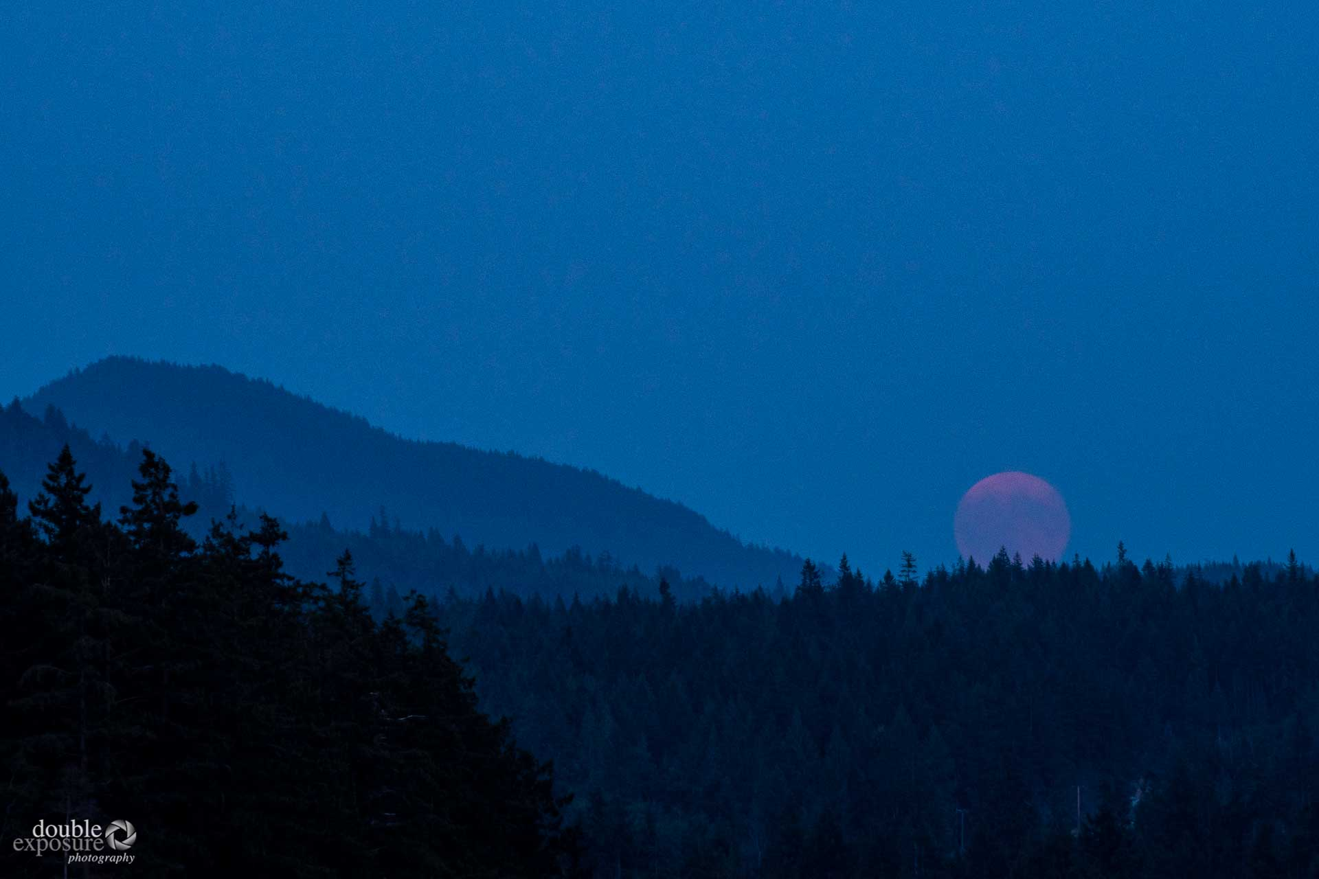 A full moon rises in a smoky sky.
