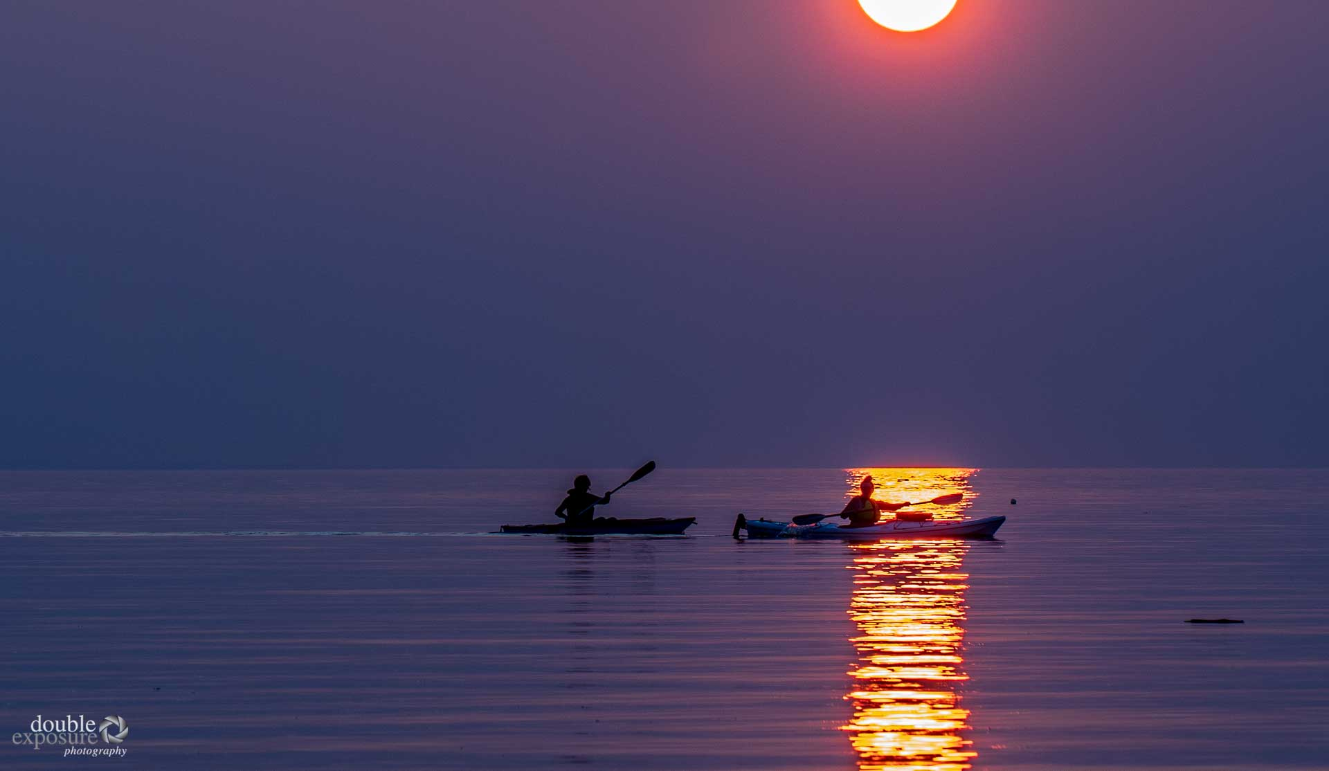 Kayakers in the light of the setting sun.